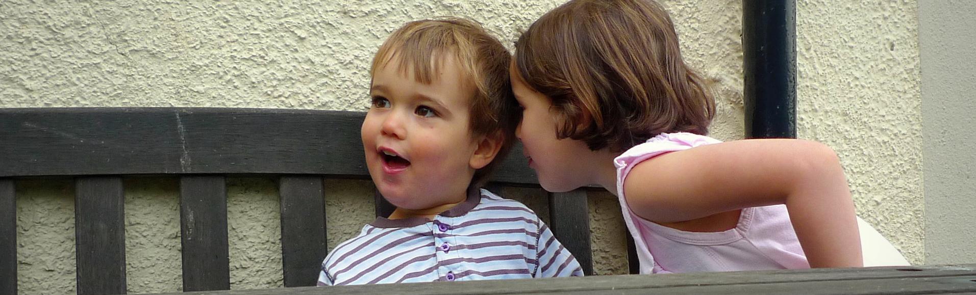 Zwei Kinder flüstern sich etwas zu.