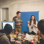 Zwischenpräsentation in einem Hackathon Team: Der Tisch sieht voll und nach Arbeit aus