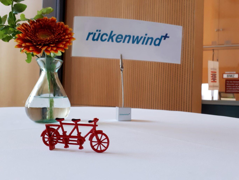 """Das rote Caritas Miniaturtandem steht im Vordergrund auf einem Tisch, im Hinergrund ist links eine Case mit einer Blume und rechts ein Schild mit der Aufschrift """"rückendwind+"""" zu sehen."""