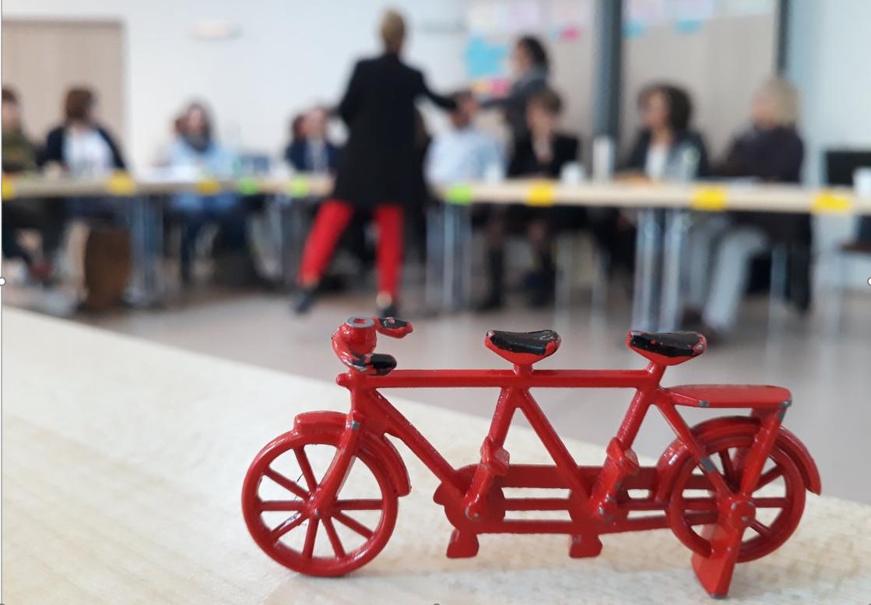 Im Vordergrund das Projektsymbol, ein Miniaturtandem, dahinter unscharf Teilnehmende im Workshop